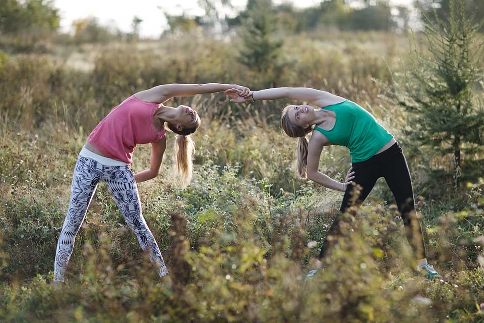 two athletic young women in Class of yoga in mas torroella